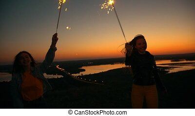 Two happy young women dancing with sparklers on a hill at...