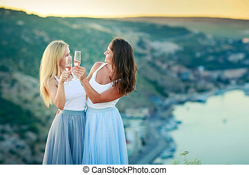 Two happy young women drinking together and having fun on top of a mountain