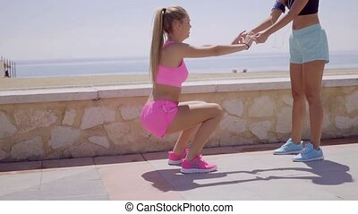 Two happy young women exercising together - Two happy...