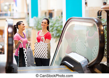 two happy young women in shopping mall