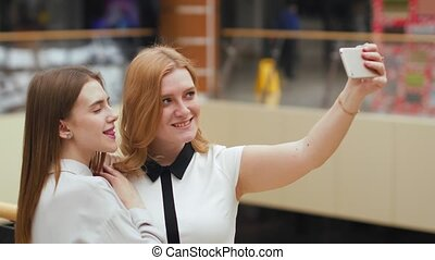 Two happy young women making selfie in the mall. Cute female...