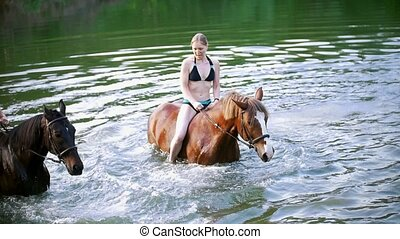 Two happy young women ride on the horse having fun in the river
