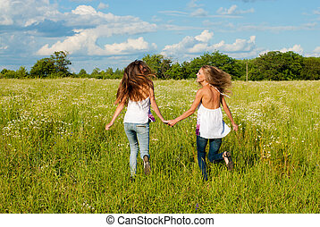 Two happy young women running on green field under blue sky