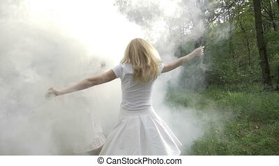 Two happy young women spinning and dancing in the forest through smoke in slow motion