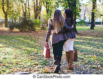 Two happy young women strolling arm in arm