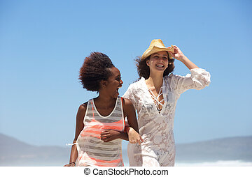 Two happy young women walking at the beach together