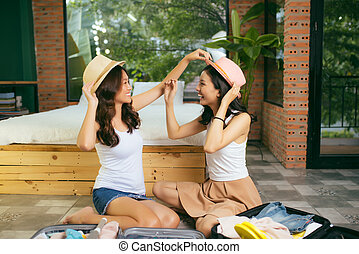 Two happy young women while packing suitcases at home for vacation or trip