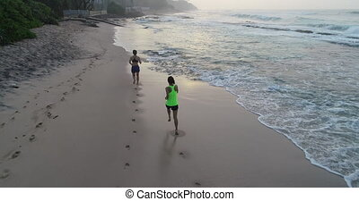 Two healthy lifestyle young women friends running on...