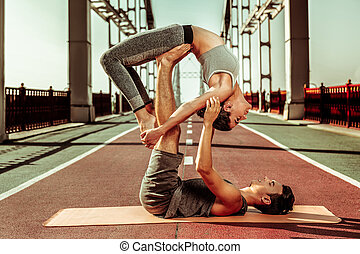 Two healthy people performing a flying wheel pose