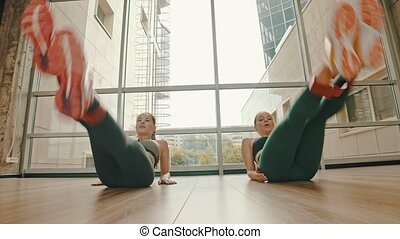 Two healthy women training their legs using a stretching strap between ankles. Mid shot