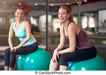 Two healthy young women with pilates balls - Two healthy...