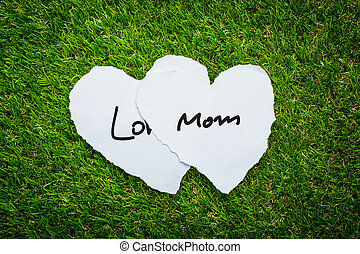 Two heart paper on green grass background with words Love Mom