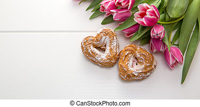 Two heart shaped cake and a bouquet of beautiful tulips on wooden background.
