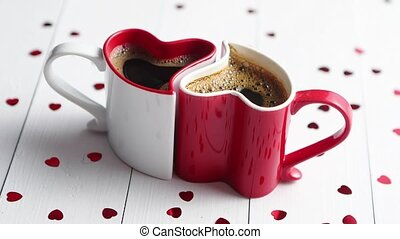 Two heart shaped coffee cups conected with each other. -...