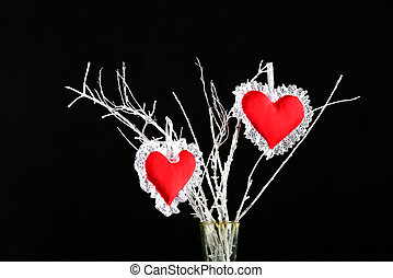 Two heart shaped red pin cushions on a tree branch