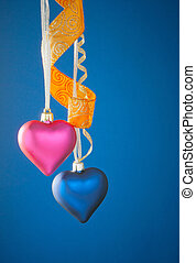 Two heart shaped toys hanging against blue background