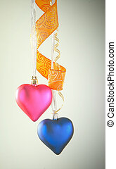 Two heart shaped toys hanging against light background