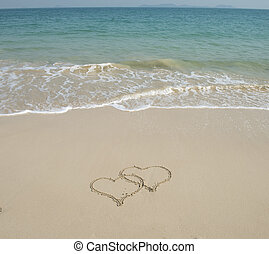 Two hearts drawn in sand at the beach