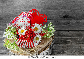 Two hearts in a wicker basket with berries and flowers on Valentine's Day in a rustic style.