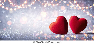 Two Hearts In Love On Silver Glitter With Abstract Defocused Background