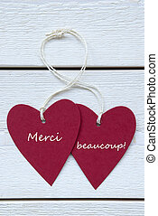 Vertical Image Two Red Hearts Label With White Ribbon On White Wooden Background With French Text Merci Beaucoupe Means Thank You Vintage Retro Or Rustic Style