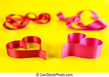 Two hearts made from pink and red, satin ribbon on yellow background. Valentines Day concept.