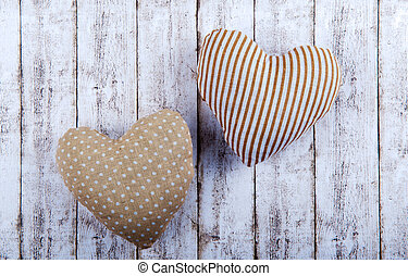 Two hearts made ??of cloth on a wooden background