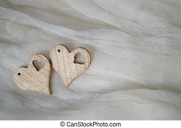 Two hearts of wood on a silk background