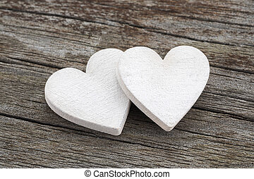 Two hearts on old wooden background