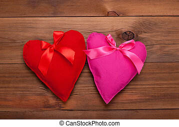 Two hearts with ribbon on wooden background.