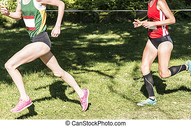 Two high school girls racing a 5K on a grass field