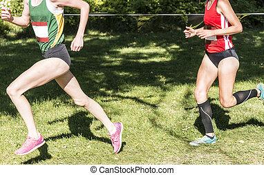 Two high school girls racing a 5K on a grass field