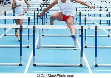 Two high school girls racing in the 100 meter hurdles