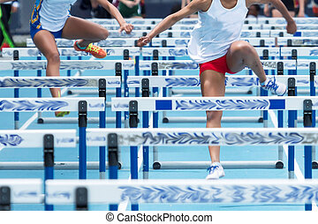 Two high school girls racing the hurdles at a track meet