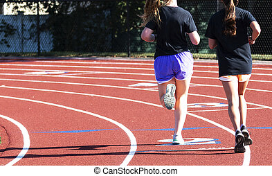 Two high school girls running on the turn on a track