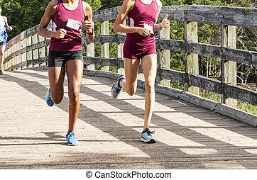 Two high school girls running over a bridge during race