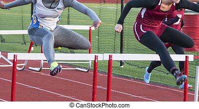 Two high school teenage girls racing in the hurdles