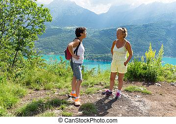 Two hiker women talking near of Lake Annecy