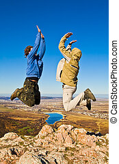 Two hikers jumping cheerfully on mountain summit in clear...