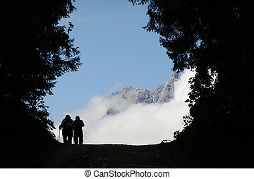 two hikers on their way in front of mountain panorama