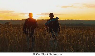 Two hikers with backpacks nature a peak on cloud sky background slow motion video. Traveler successful young men walking on top of and waiting for sunrise. man travel tourists in the mountains lifestyle concept