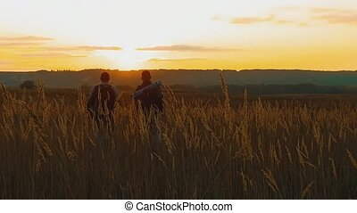 Two hikers with backpacks nature a peak on cloud sky background slow motion video. Traveler successful young men walking on top of and waiting for sunrise. man travel tourists in lifestyle the mountains concept