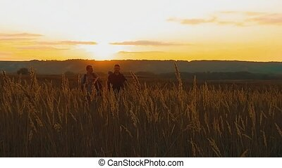Two hikers with backpacks nature a peak on cloud sky background slow motion video. Traveler successful young men walking on top of and waiting for sunrise. man travel tourists lifestyle in the mountains concept