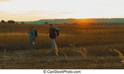 Two hikers with backpacks nature a peak on cloud sky background slow motion video. Traveler successful young men walking on top of and waiting for sunrise lifestyle. man travel tourists in the mountains concept