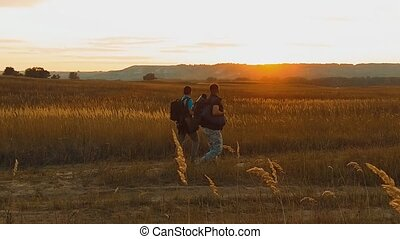 Two hikers with backpacks nature a peak on cloud sky background slow motion video. Traveler successful young men walking on top of and waiting for sunrise. man lifestyle travel tourists in the mountains concept
