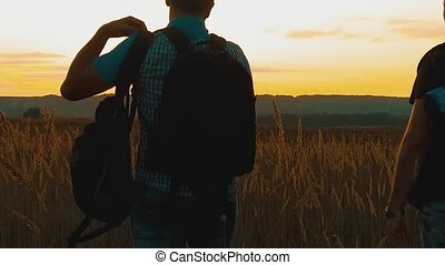 Two hikers with backpacks nature a peak on cloud sky background slow motion video. Traveler successful young men walking on top of and waiting for sunrise. man travel tourists in the mountains concept lifestyle