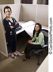 Two hispanic businesswomen meeting in cubicle