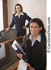 Two hispanic businesswomen standing in boardroom
