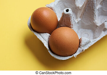 two homemade organic chicken eggs in a cardboard box on a yellow background