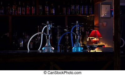 Two hookahs stand on the bar counter in a hookah bar in the dark, slow motion.
